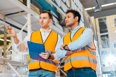 attentive multicultural warehouse workers in safety vests working in plumbing department