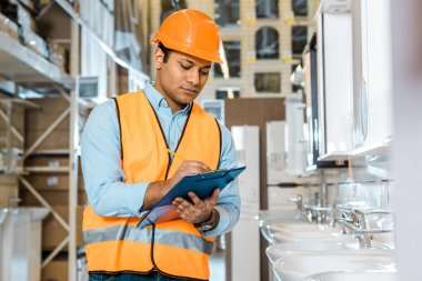 selective focus of serious indian worker writing in clipboard in plumbing department