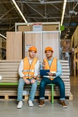 thoughtful multicultural workers in safety vests and helmets sitting on bench in warehouse