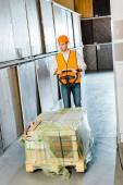 Handyter, seriöser Arbeiter, der Palettenheber mit Baumaterialien trägt