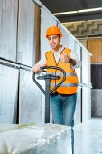 smiling worker carrying pallet jack and showing thumb up