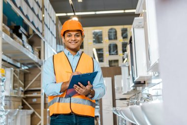 cheerful indian warehouse worker writing in clipboard, smiling and looking at camera