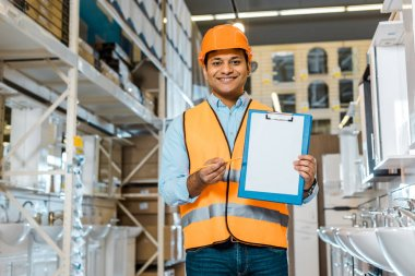 smiling indian warehouse worker showing clipboard with blank paper and looking at camera