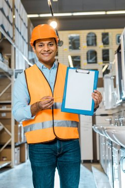 smiling indian worker pointing at clipboard with blank paper and looking at camera