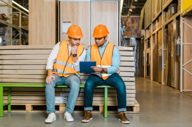 Concentrated multicultural workers sitting on bench in warehouse and looking at clipboard stock vector