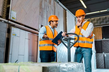upset warehouse worker with pallet jack standing near angry yelling indian colleague