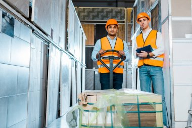concentrated multicultural warehouse workers standing near pallet jack in warehouse