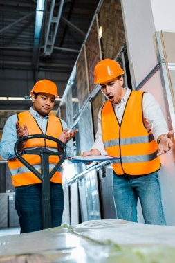 selective focus of angry warehouse worker yelling near indian colleague