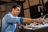 Fotografia selective focus of smiling mixed race sound producer working at mixing console in recording studio