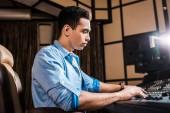 koncentrált vegyes faji hang producer dolgozik keverőpult a stúdióban