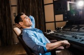 Photo smiling mixed race sound producer relaxing in office chair in recording studio