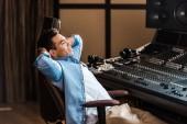 Fényképek jóképű mosolygós vegyes verseny hang producer pihenő irodaszékben a stúdióban