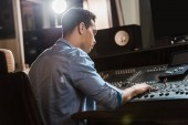 Photo concentrated mixed race sound producer working at mixing console