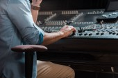 Photo cropped view of mixed race sound producer working at mixing console
