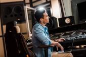 pohledný usměvavý rasový producent pracující v nahrávacích ateliéru na mixážní konzoli