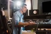 Fényképek szép koncentrált vegyes verseny hang producer dolgozó stúdióban keverőpult