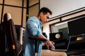 vážně smíšený producent zvuku ve smíšené rasové aplikaci používající přenosný počítač v nahrávacích studiu