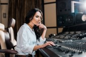 Photo beautiful concentrated sound producer working at mixing console in recording studio