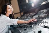Fényképek szelektíven összpontosít, vonzó hang producer dolgozó mixer konzol