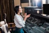 atraktivní, usmívající se producent, tleskání v nahrávacích ateliéru blízko míchací konzoly
