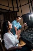 dva šťastní multikulturní výrobci, kteří vykazují úspěšné gesto v nahrávacích ateliéru
