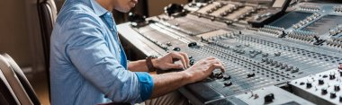 panoramic shot of mixed race sound producer working at mixing console in recording studio