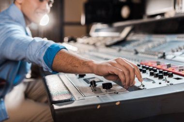 selective focus of mixed race sound producer working at mixing console