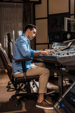 attentive mixed race sound producer working at mixing console in recording studio