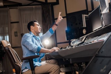 handsome mixed race sound producer showing victory sign while working in recording studio