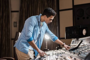 concentrated sound producer working at mixing console in recording studio