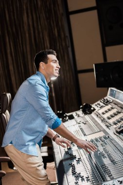 smiling mixed race musician working at mixing console in recording studio