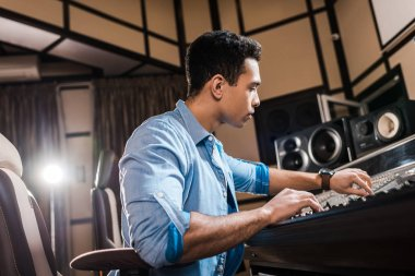 Handsome mixed race musician working at mixing console in recording studio stock vector
