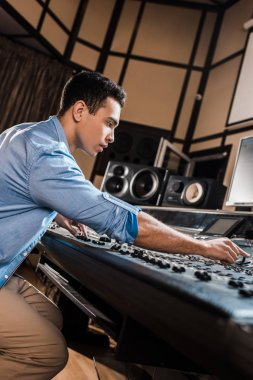 serious mixed race sound producer working in recording studio