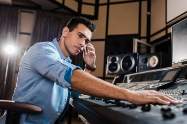 handsome, attentive mixed race sound producer working at mixing console