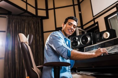 Cheerful mixed race sound producer sitting in office chair in recording studio and looking at camera stock vector