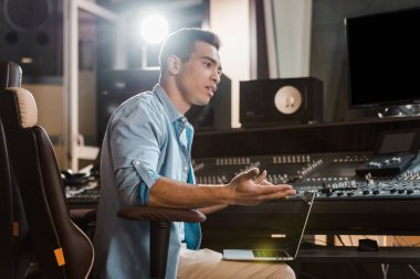 handsome concentrated mixed race sound producer working in recording studio at mixing console