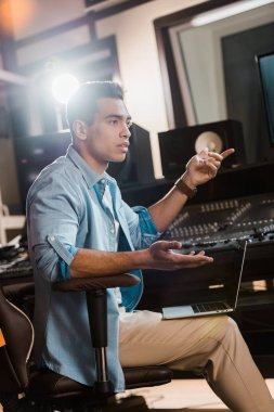 serious mixed race sound producer gesturing while sitting at  mixing console in recording studio