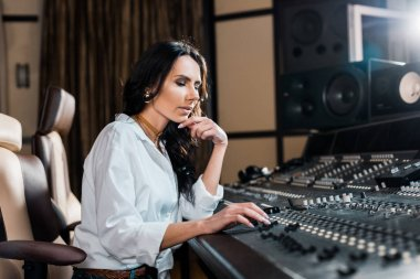 Beautiful concentrated sound producer working at mixing console in recording studio stock vector