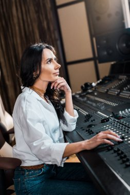 beautiful sound producer working on mixer console in recording studio