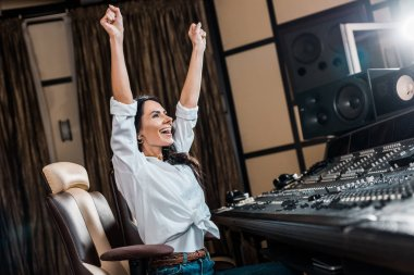 happy sound producer showing success gesture near mixing console in recording studio