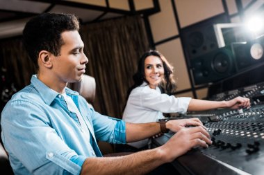 Selective focus of good-looking mixed race sound producer working at mixing console near pretty smiling colleague stock vector