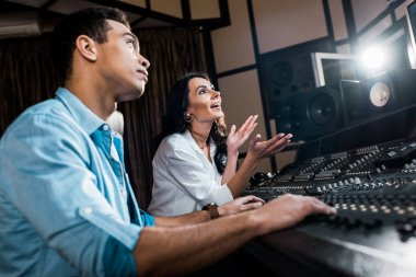 selective focus of attractive sound producer gesturing near handsome mixed raced colleague working at mixing console