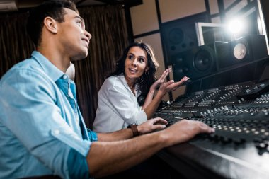 selective focus of pretty sound producer gesturing near mixed raced colleague working at mixing console