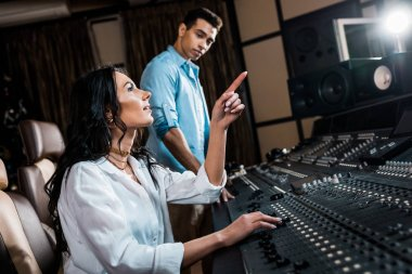 Pretty sound producer pointing with finger while working in recording studio near mixed race colleague stock vector