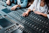 Photo cropped view of two multicultural sound producers working at mixing console in recording studio