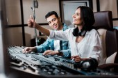 Fotografie selective focus of cheerful sound produce showing thumb up while working at mixing console near smiling mixed race friend