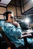 bello serio produttore di suono gara mista in occhiali da sole e cuffie seduti in studio di registrazione