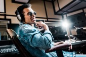 Photo smiling mixed race sound producer in headphones and sunglasses sitting in recording studio