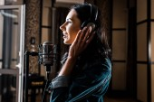 side view of beautiful woman singing near microphone in recording studio