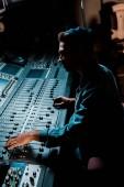 hang gyártó dolgozik keverő konzol a sötét stúdióban
